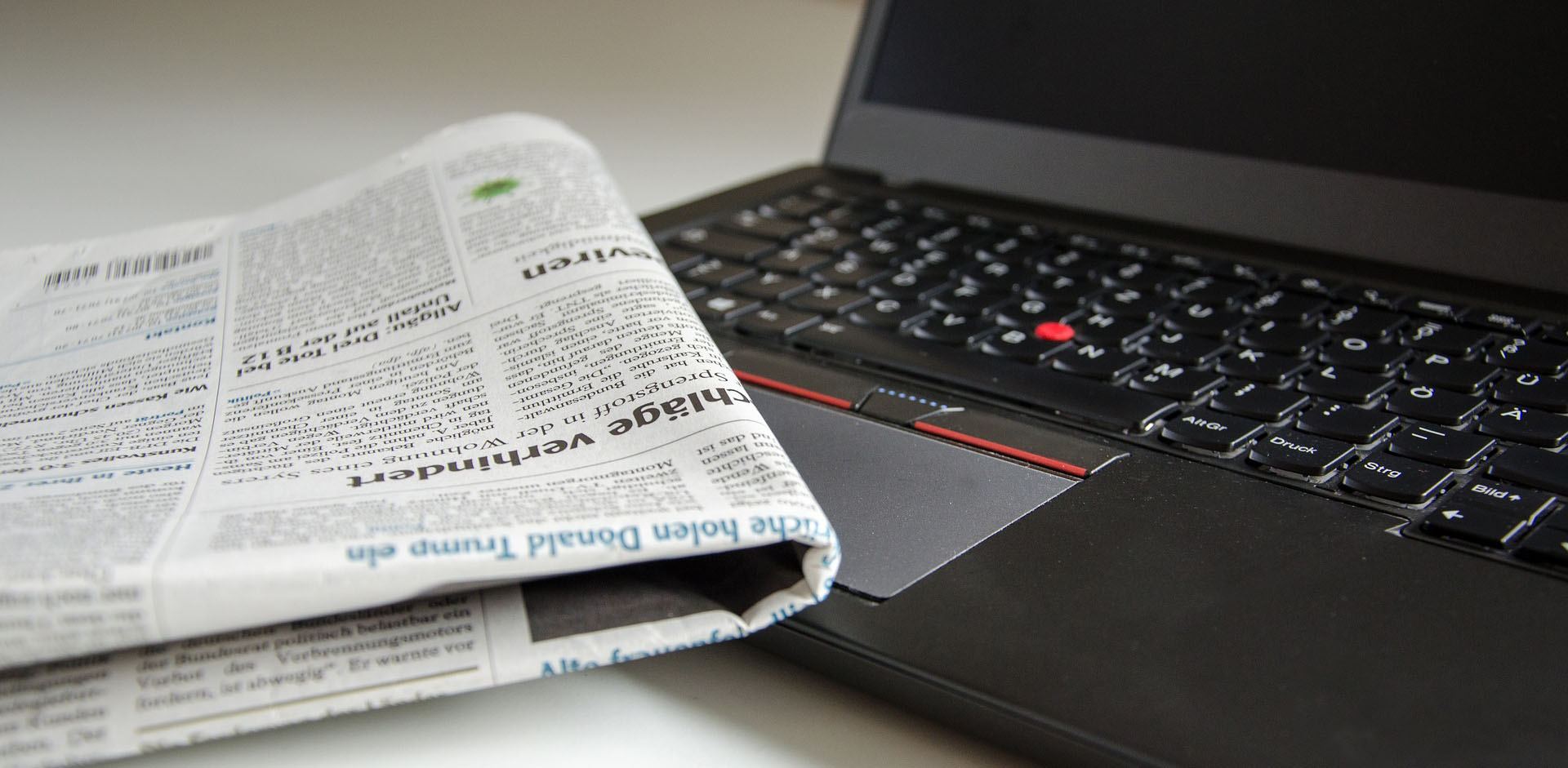 Newspaper sitting on a laptop