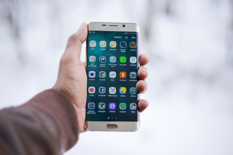 An image of a hand holding a smartphone displaying many apps.